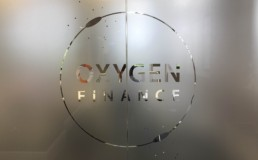 The Oxygen Finance logo on a glass partition