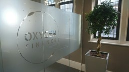 A glass partition featuring the Oxygen Finance logo with a nice office plant